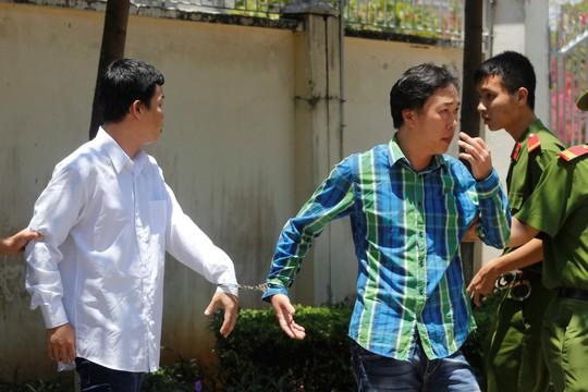 Hai bị cáo Linh (áo xanh) và Thế được đưa ra xe sau khi phiên tòa hoãn