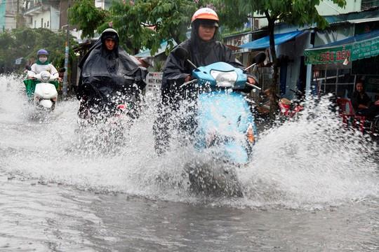 Người dân TP HCM bì bõm sau cơn mưa lớn - Ảnh 1.