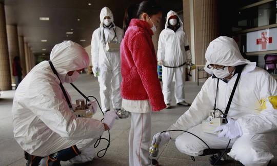 Một người sơ tán kiểm tra phóng xạ Ảnh: AP