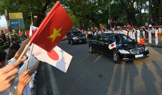Người dân TP Huế đứng hai bên đường Lê Lợi đón chào Nhật hoàng. Ảnh: Reuters