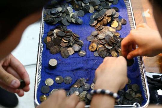 Nhiều đồng xu lấy ra từ bụng Omsin có dấu hiệu bị gặm mòn. Ảnh: Reuters