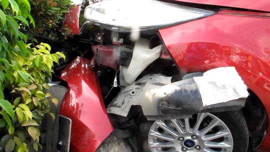 Chiếc xe máy nằm lọt trên dải phân cách và dính chặt trong đầu xe