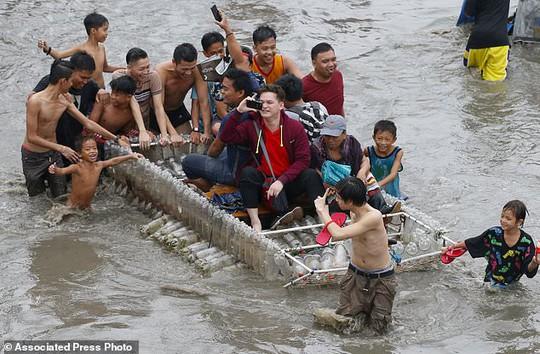 Bão vừa đổ bộ, người dân Philippines ngụp lặn trong nước lũ - Ảnh 8.