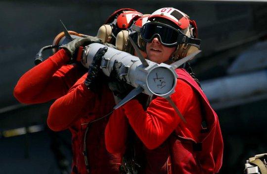Các nhân viên Hải quân Mỹ di chuyển một tên lửa trên tàu sân bay USS Carl Vinson đang tuần tra ở biển Đông. Ảnh: Reuters