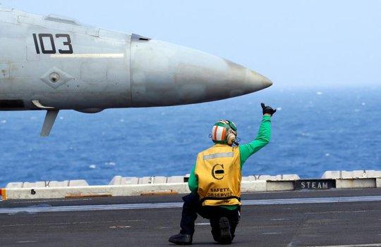 Ra tín hiệu bằng tay cho chiến đấu cơ F18 trên tàu sân bay USS Carl Vinson. Ảnh: Reuters