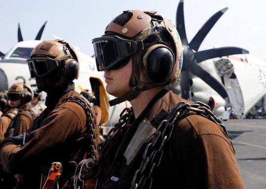 Các nhân viên của Hải quân Mỹ trên tàu sân bay USS Carl Vinson theo dõi chiến đấu cơ F18 cất cánh. Ảnh: Reuters