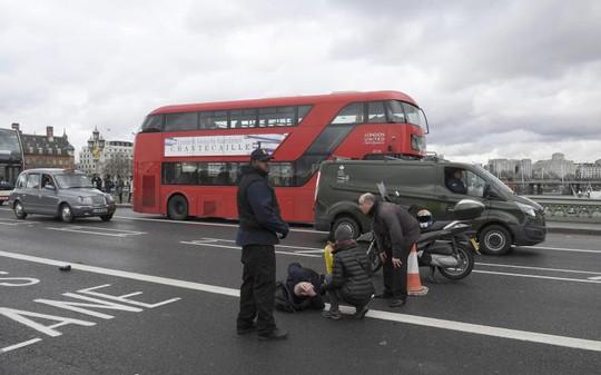 Một người đàn ông bị thương đang nằm trên cầu Westminster, London sau vụ xả súng. Ảnh: Reuters