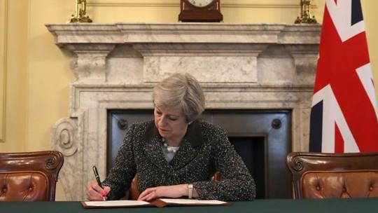 Thủ tướng Anh Theresa May ký thư chính thức khởi động tiến trình rời khỏi Liên minh châu Âu (EU) của Anh. Ảnh: PA