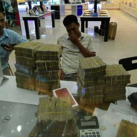 Anh Trần Trung Tín mang khoảng 50 triệu tiền lẻ tiết kiệm đi mua iPhone 7 màu đỏ. Ảnh: Trần Đình Trọng.