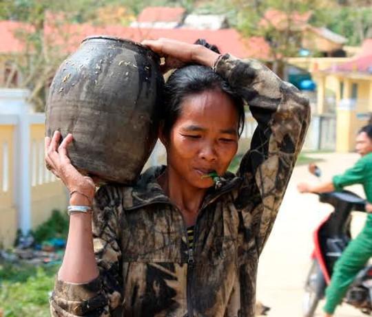 Phụ nữ A Rem với ché rượu đoác mang từ trong rừng về