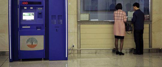 Một người đàn ông và phụ nữ đứng ở quầy bên cạnh ATM của Ngân hàng Thương mại Ryugyong tại Aân bay quốc tế Sunan. Ảnh: AP