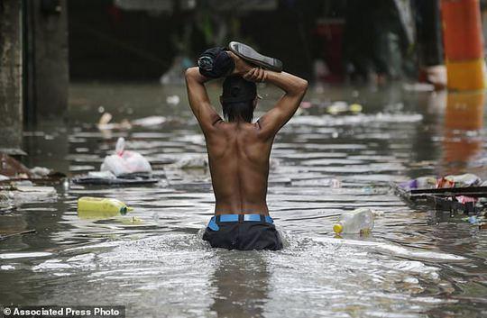 Bão vừa đổ bộ, người dân Philippines ngụp lặn trong nước lũ - Ảnh 1.