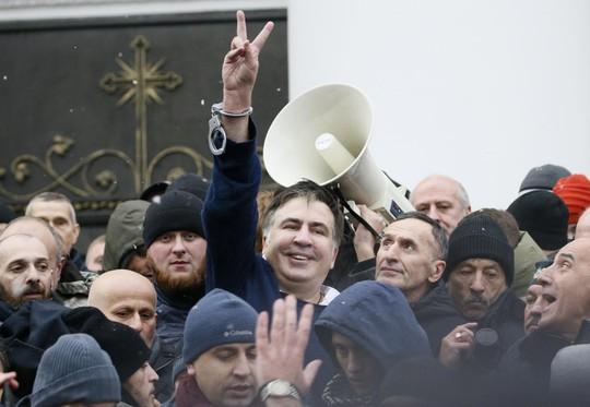 Saakashvili hoan hỉ sau khi được giải thoát khỏi xe cảnh sát. Ảnh: Reuters