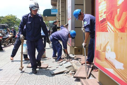Bậc tam cấp và biển hiệu của một cửa hàng bị đập bỏ, trả lại vỉa hè thông thoáng.