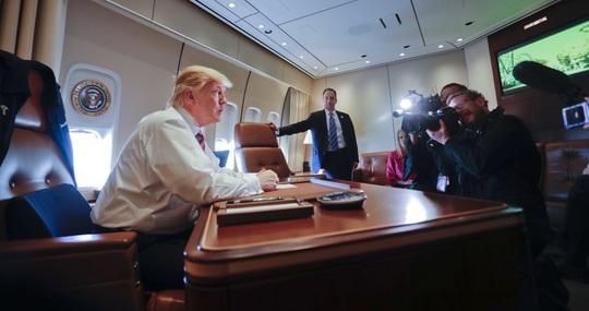 Ông Trump ngồi tại bàn làm việc trên chiếc Air Force One hôm 26-1. Ảnh: AP