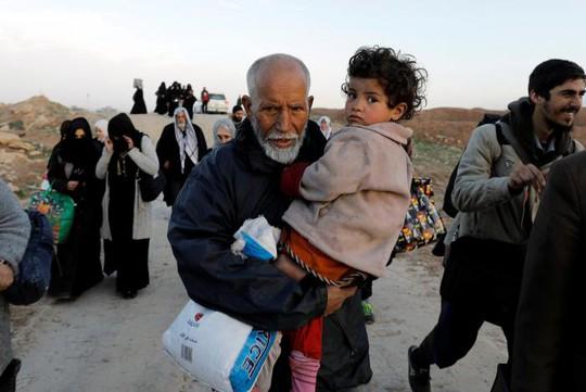 Một ông lão bế cháu gái rời khỏi nhà khi lực lượng Iraq chiến đấu với IS ở Tây Mosul ngày 8-3. Ảnh: REUTERS
