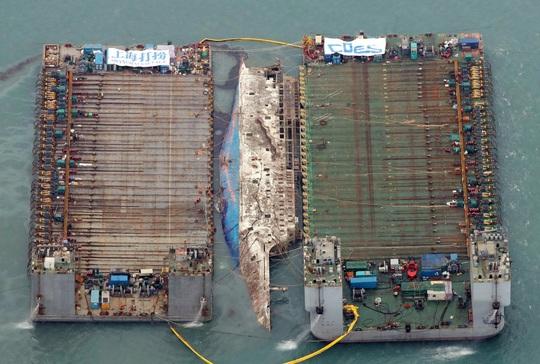 Hai sà lan nâng phà Sewol từ độ sâu 40 m ngoài khơi đảo Jindo ở Hàn Quốc lên mặt biển ngày 23-3. Ảnh: YONHAP