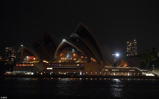 Phần đèn chiếu sáng của nhà hát nổi tiếng ở Sydney - Úc được tắt ở phần mái trong Giờ Trái đất. Ảnh: EPA