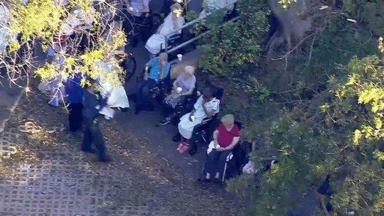 Cảnh sát sơ tán những người cao tuổi ra khỏi cơ sở. Ảnh: NBC News