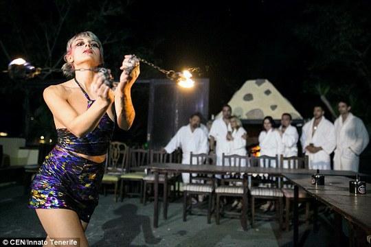 Một nhân viên nữ múa lửa bên ngoài khu vực phòng ăn. Ảnh: CEN