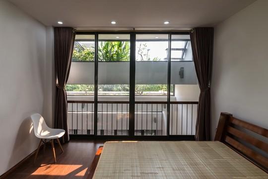 Phòng ngủ với bài trí đơn giản, mát mắt với cây xanh và cửa sổ lớn.