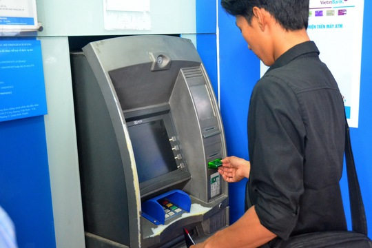 Vừa rút tiền từ ATM vừa lo - Ảnh 1.