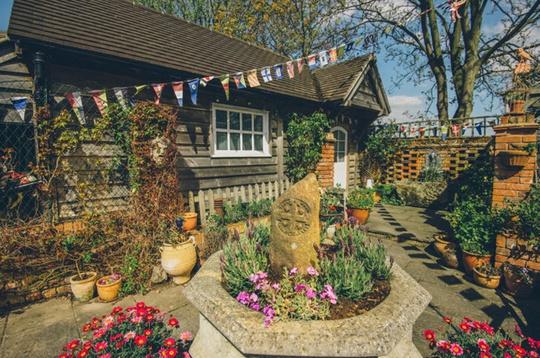 Phần sân sau nhà với hoa lá rực rỡ, tượng trang trí, đài phun nước. Hiện ngôi nhà mở cửa đón du khách vào xem.