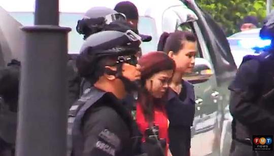 Nữ nghi phạm Indonesia (áo đỏ) bị cảnh sát áp giải. Ảnh:FMT