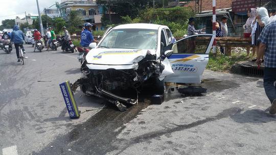 Taxi tông gãy cột điện, 3 người bị thương - Ảnh 1.