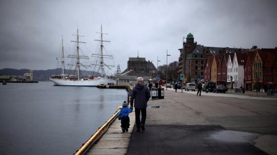 Một người đàn ông dắt một đứa trẻ dọc bến cảng thị trấn Bergen, Na Uy. Ảnh: Reuters