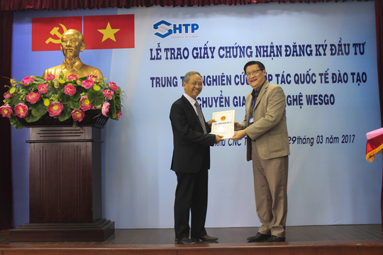 Ông Lê Hoài Quốc, Trưởng Ban Quản lý SHTP (bên phải), trao giấy chứng nhận triển khai dự án WESGO cho đại diện Trường CĐ nghề Tây Sài Gòn