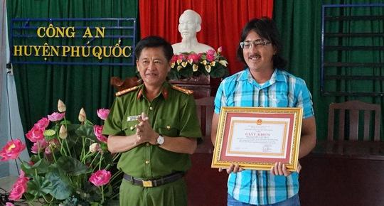 Đại tá Nguyễn Thanh Nhanh trao giấy khen của Giám đốc Công an tỉnh Kiên Giang cho anh Phát. Ảnh: CTV