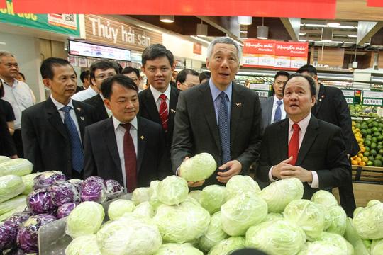 Ông cẩn thận xem từng loại và thông tin về các mặt hàng này, qua bảng thông tin của siêu thị.