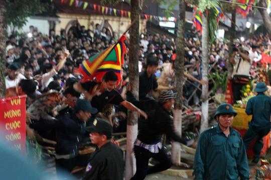 Sau nghi lễ đốt ông Tiêu, hàng ngàn người dự lễ hội tràn qua hàng rào để tranh nhau các cỗ bánh, trái cây nhằm tìm chút lộc đầu năm.