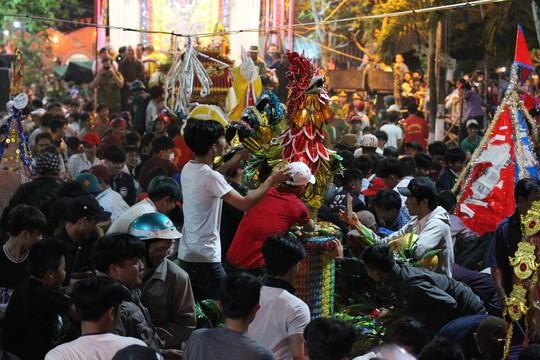 Bánh cúng trên giàn thí thực được quăng ra, các cỗ bánh được rất nhiều người vây quanh.