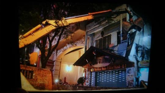Xe cẩu phá mái gỗ trang trí trước cửa 1 nhà hàng trên đường Thủ khoa Huân