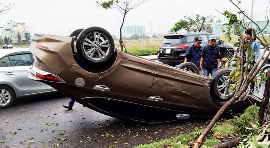 Ô tô mất lái bị lật, tài xế đạp cửa thoát thân - Ảnh 1.