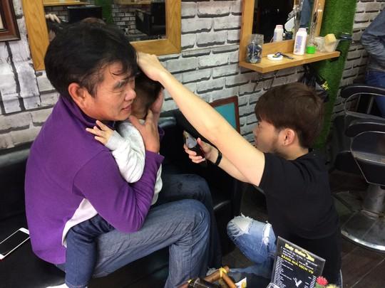 Clip: Bật cười khi HLV Phan Thanh Hùng lúng túng bế cháu cắt tóc - Ảnh 2.
