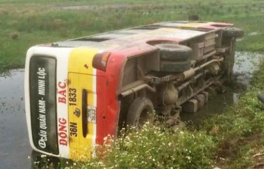 Xe buýt lật dưới ruộng, nhiều người đầy bùn đất thoát khỏi xe - Ảnh 1.