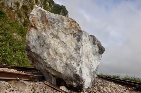 Mưa lớn, nhiều tảng đá trăm tấn rơi xuống chắn ngang đường sắt - Ảnh 1.