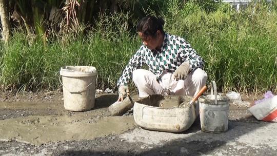 Người phụ nữ nghèo hơn 10 năm bỏ tiền túi vá đường - Ảnh 1.