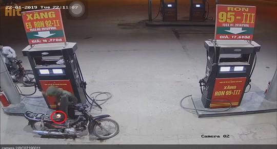 Nam thanh niên dùng bật lửa kiểm tra xăng vừa đổ vào xe máy tại cây xăng - Ảnh 2.
