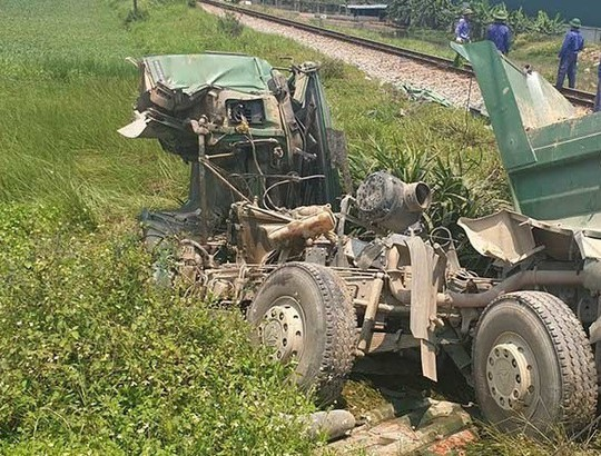 Tàu hỏa tông xe ben bay xa 10 m, tài xế tử vong trong cabin bẹp nát - Ảnh 1.