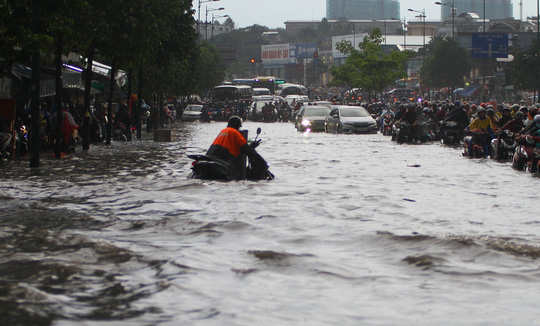 CLIP: Nước cuồn cuộn cuốn ngã xe máy trong cơn mưa xối xả ở TP HCM - Ảnh 2.
