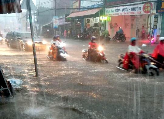CLIP: Nước cuồn cuộn cuốn ngã xe máy trong cơn mưa xối xả ở TP HCM - Ảnh 5.