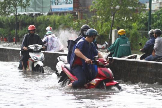 CLIP: Nước cuồn cuộn cuốn ngã xe máy trong cơn mưa xối xả ở TP HCM - Ảnh 3.