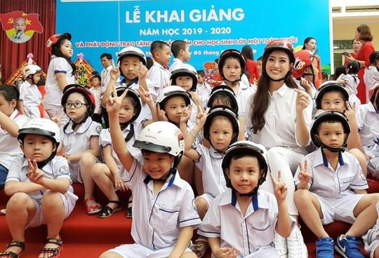 Hoa hậu Lương Thùy Linh trao mũ bảo hiểm cho học sinh trong ngày khai giảng - Ảnh 12.