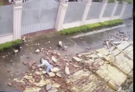 CLIP: Cô gái đi bộ trong bão số 9 bị tường gạch đè gây thương tích nặng - Ảnh 1.