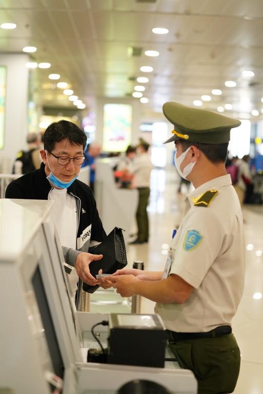 Dòng người đeo khẩu trang tại sân bay Nội Bài - Ảnh 9.
