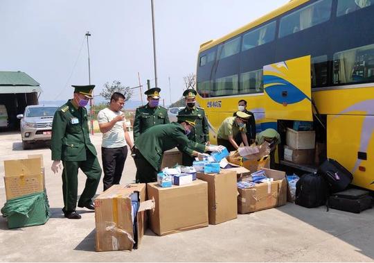 Xe khách vận chuyển gần 30.000 khẩu trang y tế, 98 bộ đồ bảo hộ y tế từ Việt Nam sang Lào - Ảnh 2.